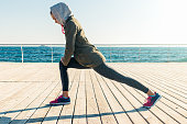 Woman in jacket and hood doing sports exercises on the beach in the morning, wide angle