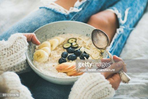 Mujer en pantalones vaqueros y un suéter de comer avena saludable porriage : Foto de stock