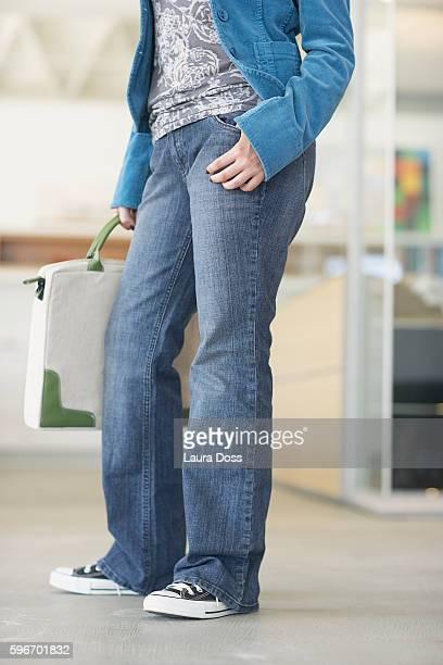 Woman in jeans carrying a briefcase
