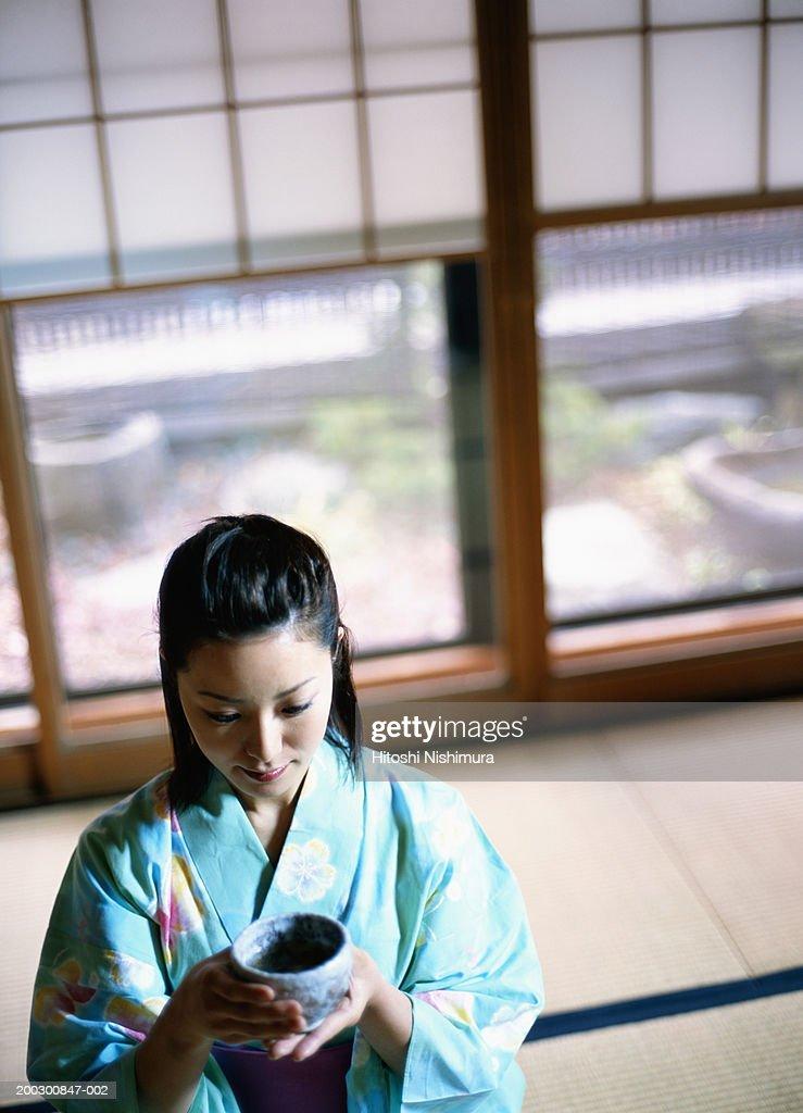 Woman in kimono holding bowl : Stock Photo