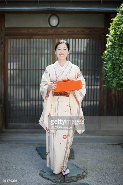 Woman in kimono holding gift, smiling