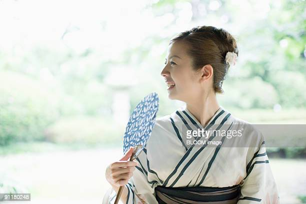 Woman in kimono holding paper fan, smiling, looking away