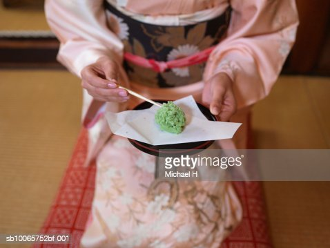Woman in kimono holding small cake on plate : Stock Photo