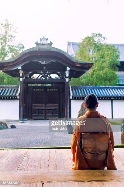 Woman in kimono kneeling at temple in early morning