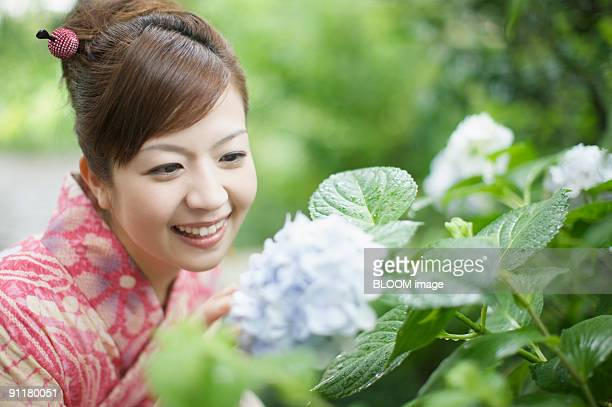 Woman in kimono looking at hydrangea, smiling