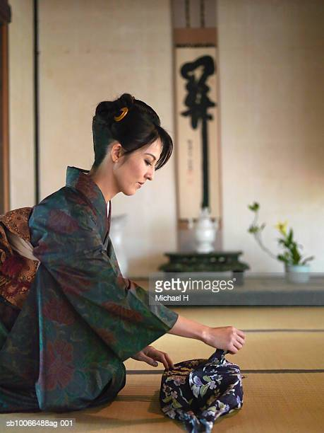 Woman in kimono opening gift in temple