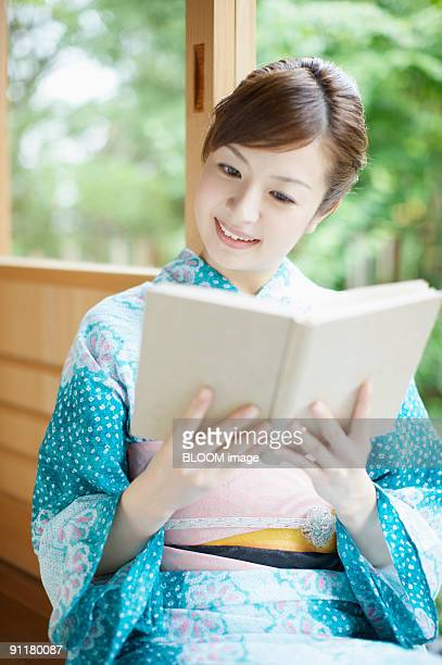 Woman in kimono reading book