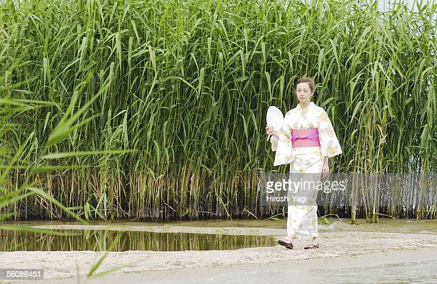 A woman in kimono walking on lake side