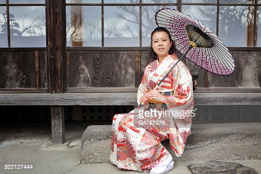 Woman in kimono with umbrella against traditional Japanese house
