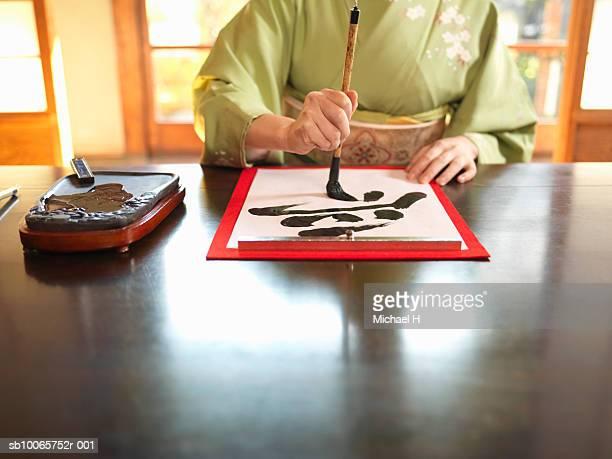 Woman in kimono writing calligraphy
