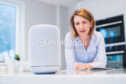 Woman In Kitchen Asking Digital Assistant Question : Stock Photo