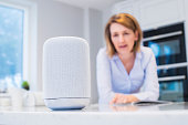 Woman In Kitchen Asking Digital Assistant Question