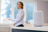 Woman In Kitchen Asking Digital Assistant Whilst Washing Up