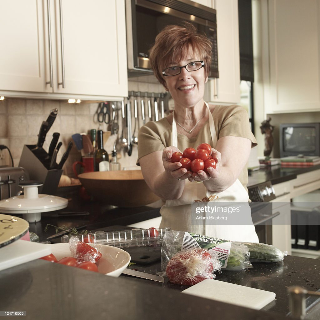 Woman in kitchen cooking, offering tomatoes : Stock Photo