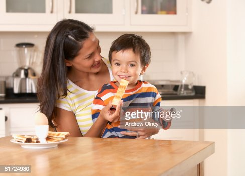 Woman in kitchen feeding young boy a piece of toast and smiling : Stock Photo