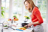 Woman In Kitchen Following Recipe On Digital Tablet To Make A Meal