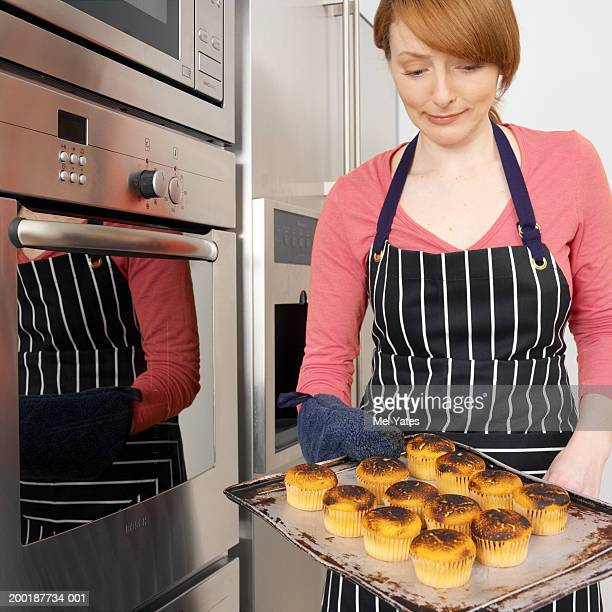 Woman in kitchen holding baking tray of burnt cup cakes