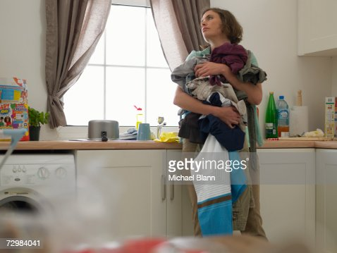 'Woman in kitchen holding laundry, looking careworn'