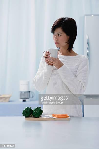 Woman in kitchen, holding mug, looking away