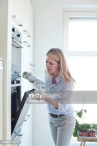 Woman in kitchen looking into oven