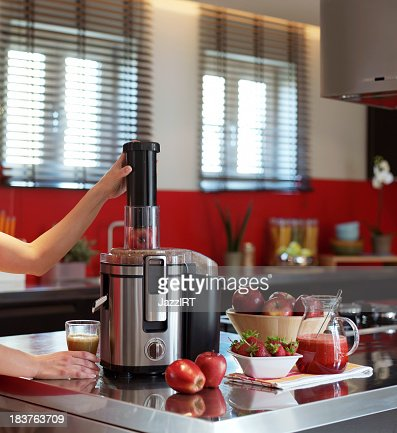 Woman in kitchen making fresh squeezed juice using