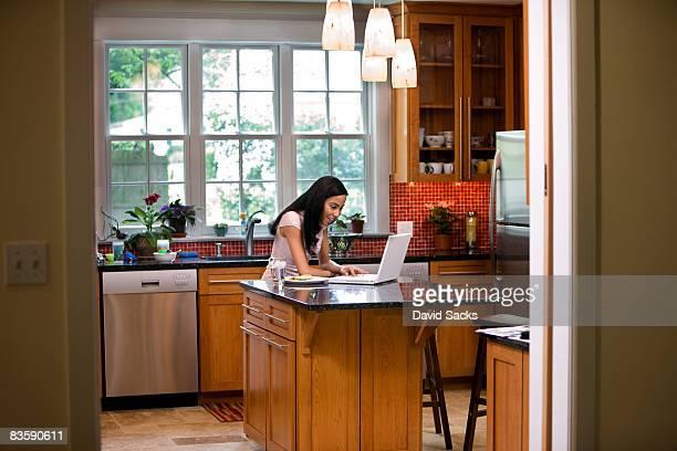 Frau in der Küche mit laptop