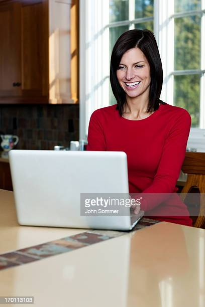 Woman in kitchen on notebook computer