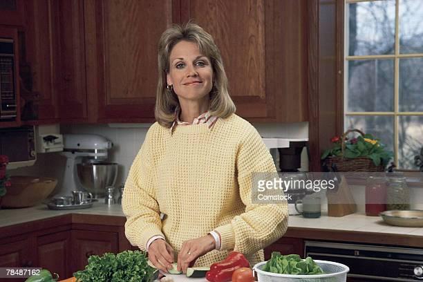 Woman in kitchen preparing salad