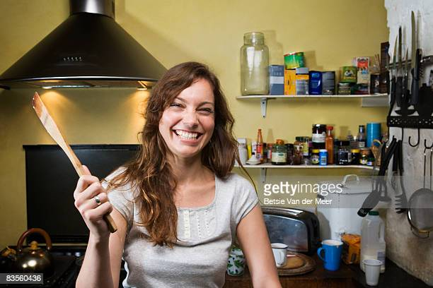 Woman in kitchen, waving with spoon.