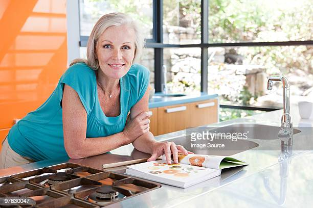 Woman in kitchen with cookbook