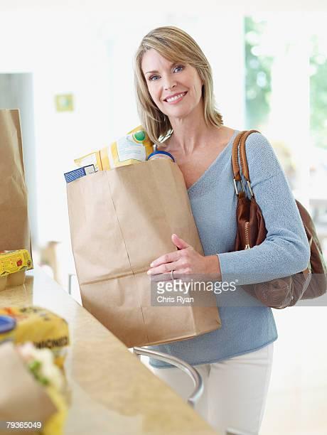 Mujer en cocina con bolsas de comestibles