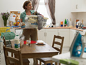 Woman in kitchen with laundry basket and dirty crockery