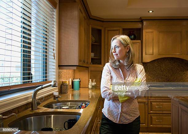 Woman in kitchen with plastic gloves