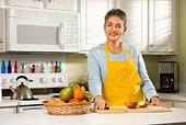 Woman in kitchen with sliced apple