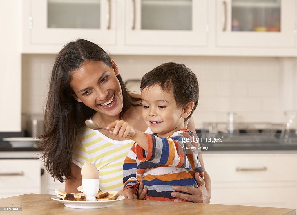 Woman in kitchen with young boy eating a boiled egg and toast : Stock Photo