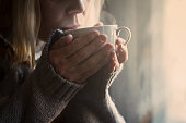 Woman in grey knitted sweater with traditional motifs drinking  a white cup of hot coffee with steam coming out in the morning light