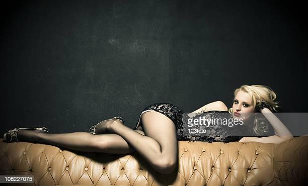 Femme en dentelle et posant allongé sur un canapé