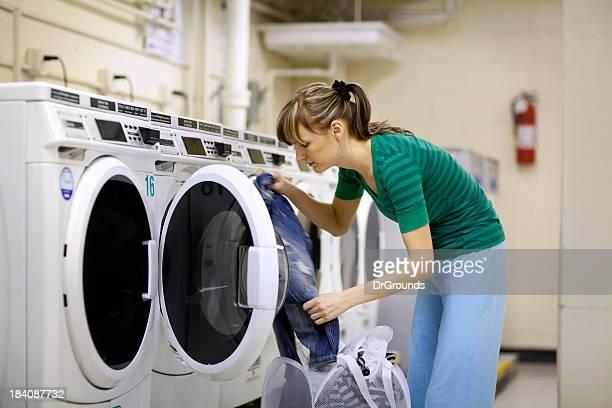 Femme de laverie Chargement des vêtements dans la machine à laver