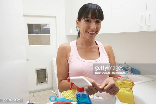 Woman in laundry room holding cleaning box, smiling, portrait
