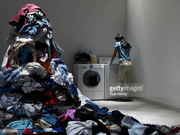 Woman in laundry room next to pile of clote