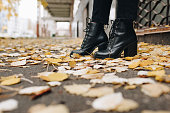 cropped shot of woman in stylish leather boots standing on road covered with fallen leaves