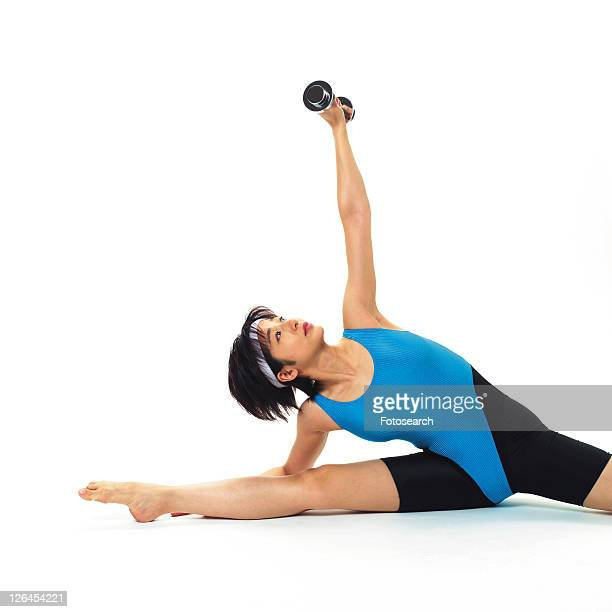 A woman in Leotard exercising with a dumbbell, Front View, Copy Space