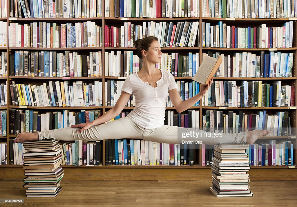 Woman in library reads book and holds yoga pose : Stock-Foto