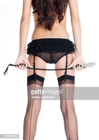 Woman in lingerie holding riding crop