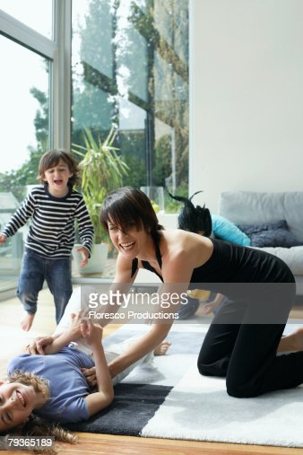 Woman in living room playing with three young kids : Stock Photo