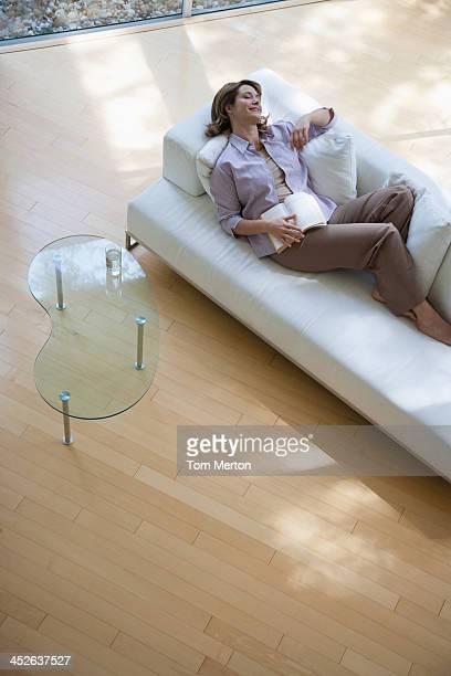 Frau im Wohnzimmer Schlafen auf sofa hält Buch