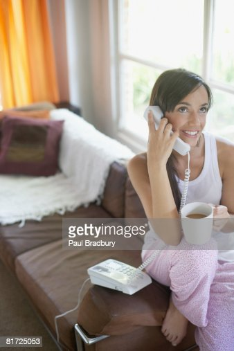 Donna nel salotto con telefono e bere caffè