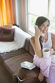 Woman in living room using telephone and drinking coffee
