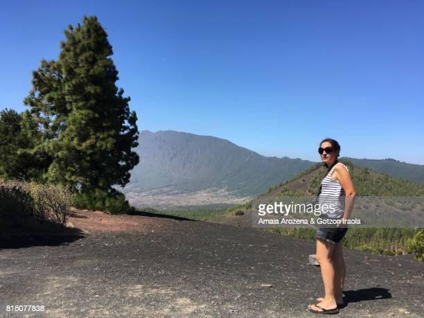 Woman in Llano del Jable volcanic landscape and Caldera de Taburiente in the background. La Palma island, Canary islands, Spain.