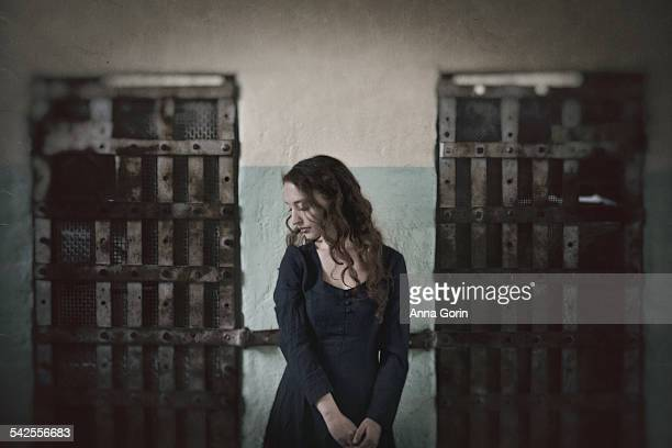 Woman in long dress in old prison, textured